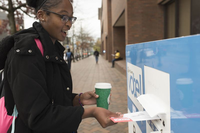 Woman placing ballot into drop box.